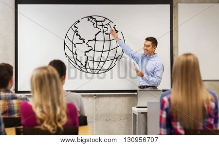 education, high school, teaching, geography and people concept - group of students and happy teacher with notepad showing earth globe drawing on white board in classroom