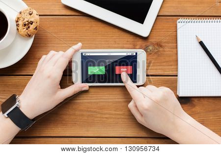 technology, business, people and communication concept - close up of woman with incoming call on smartphone screen and coffee cup on wooden table