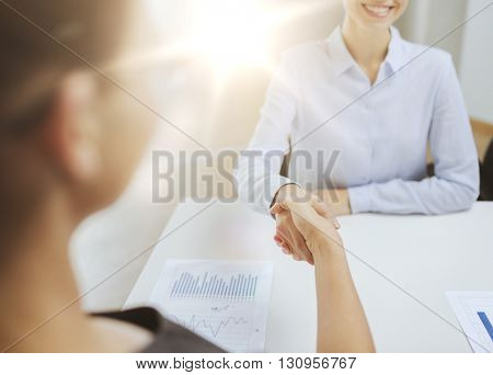business and office concept - two smiling businesswoman shaking hands in office