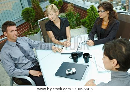 Group of young business people sitting around table on office terrace outdoor, talking and working together. Overhead view.