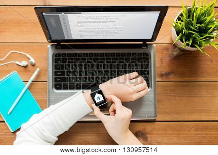 communication, business, people and technology concept - close up of woman with smart watch and laptop computer on wooden table with e-mail message and coding on screens