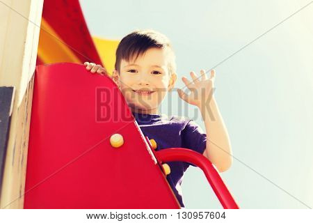 summer, childhood, leisure, gesture and people concept - happy little boy waving hand on children playground climbing frame