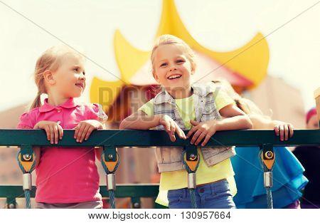 summer, childhood, leisure, friendship and people concept - happy little girls on children playground climbing frame