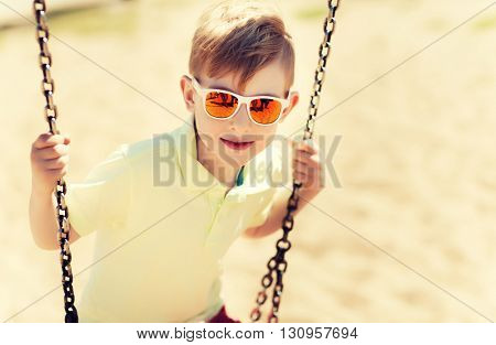 summer, childhood, leisure, friendship and people concept - happy little boy in sunglasses swinging on swing at children playground