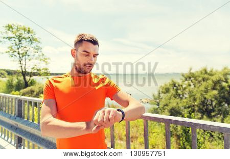 fitness, sport, people and healthy lifestyle concept - young man with smart wristwatch at summer seaside