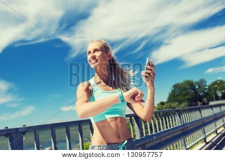 fitness, sport, people, technology and healthy lifestyle concept - smiling young woman with heart rate watch and smartphone exercising outdoors
