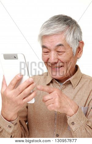 portrait of senior Japanese man using tablet computer on white background