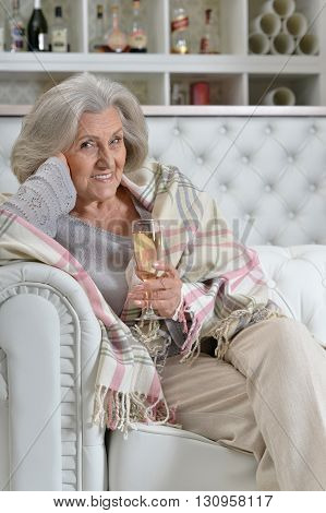happy Senior woman resting at home with glass of wine