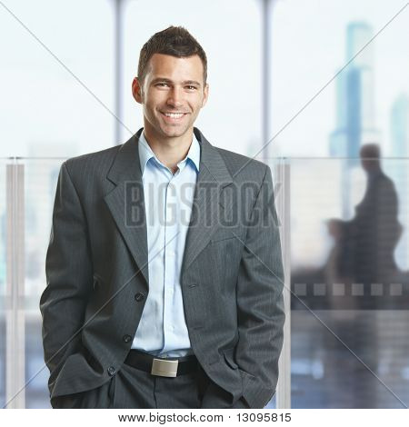 Casual businessman standing with hands in pocket in corporate office lobby, smiling.