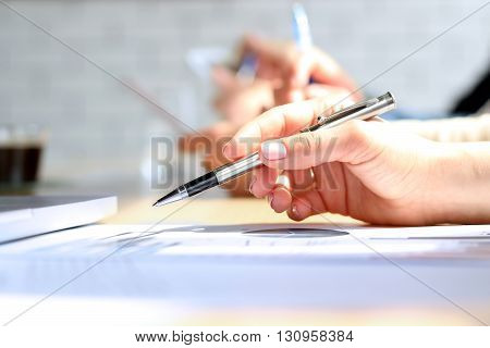 Close-up Of Businesswoman Analyzing Graph with collegues