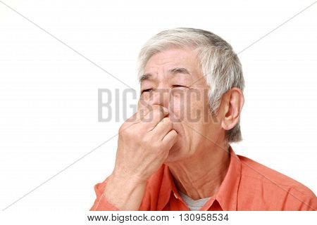 senior Japanese man holding his nose because of a bad smell