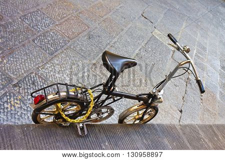 Small black bicycle parked on a street paved with stone