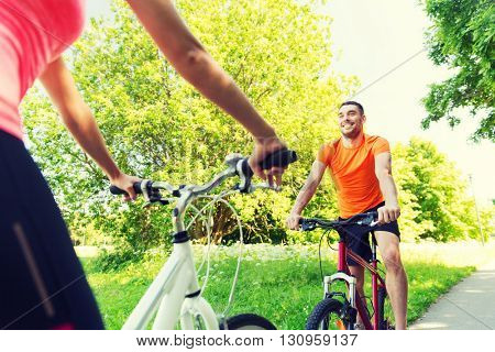 fitness, sport, people and healthy lifestyle concept - close up of happy couple riding bicycle outdoors at summer
