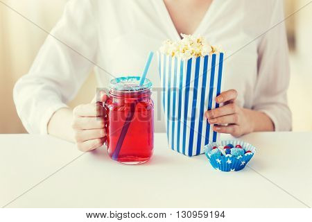american independence day, celebration, patriotism and holidays concept - close up of woman eating popcorn with drink in glass mason jar and candies at 4th july party