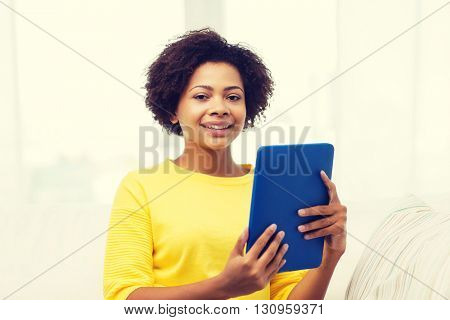 people, technology and leisure concept - happy african american young woman sitting on sofa with tablet pc computer at home