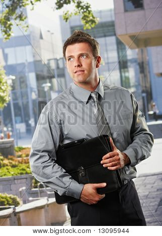 Smiling businessman holding briefcase standing outside office building in sunshine.