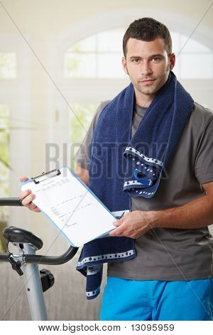 Man standing beside stationary bike showing training plan.