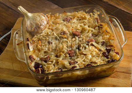 Baked sauerkraut with sausages on wooded table