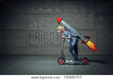 Boy with a rocket on scooter in studio
