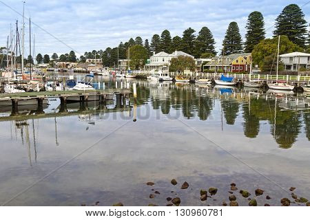 PORT FAIRY, AUSTRALIA - APRIL, 2016 : Boats moored next to beautiful modern houses along the Moyne River at Port Fairy in Victoria, Australia on April 13, 2016