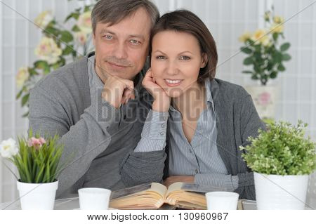 Beautiful smiling couple sitting at table reading a book