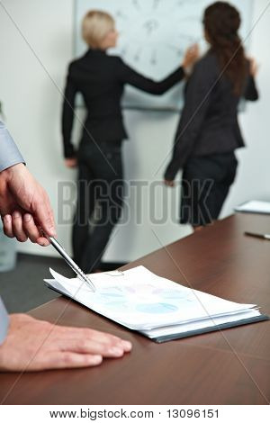 Hand showing chart on meeting table, business people talking at whiteboard in background.