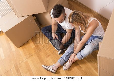 Young couple in love moving in a new apartment sitting on the floor planning to redecorate their new home. Top view