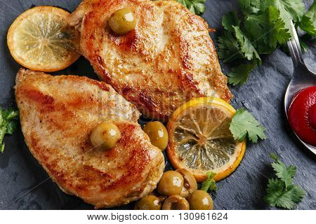 roasted chicken breast with lemon on black stone