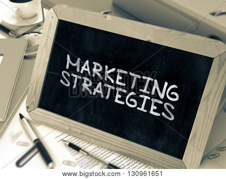 Marketing Strategies - Chalkboard with Hand Drawn Text, Stack of Office Folders, Stationery, Reports on Blurred Background. Toned Image. 3D Render.