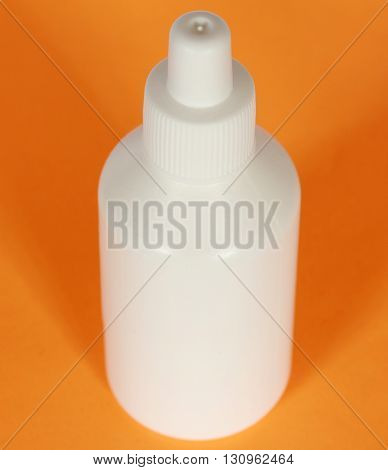 White plastic bottle on an orange background.