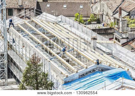 Udine,Italy - April 28 2016 : Construction site. Construction crew working on the roof sheeting.