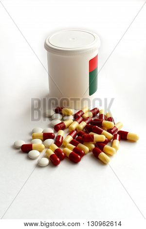 pill bottle and a heap of colorful scattered pills on white background vertical