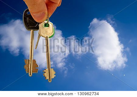 The apartment keys in hand in the background against the sky and clouds