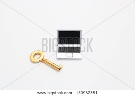 Laptop and key. Miniature notebook PC and key on white background.