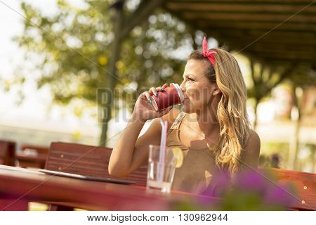 Beautiful blond girl sitting in an outdoor cafe holding a take-away cup of coffee and pensively looking into the distance