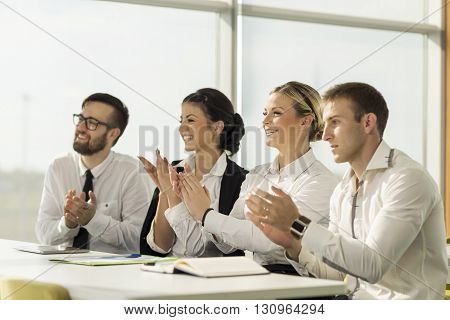 Business team applauding a colleague on a successful presentation
