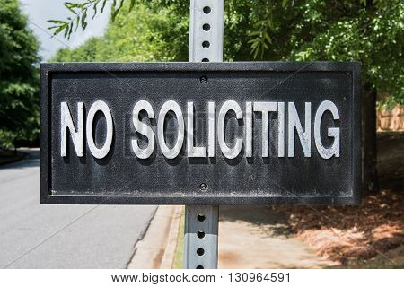 No Soliciting Sign hangs on a metal post in suburban neighborhood