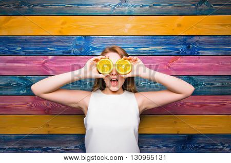 Young girl holds half of a juicy orange. Surprised face. Young girl on a colorful striped background. Fruit fashion girl. Full face. Bright juicy picture