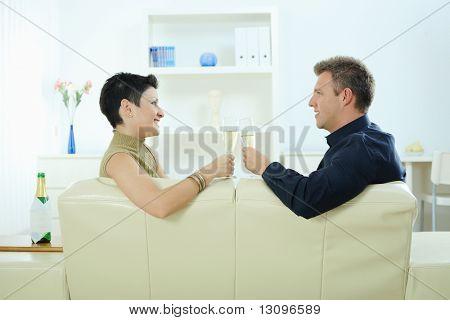Amor pareja tintineo champagne gafas en casa en el sofá. Sonriendo y mirando el uno al otro.