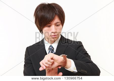 young Japanese businessman checking time on his watch