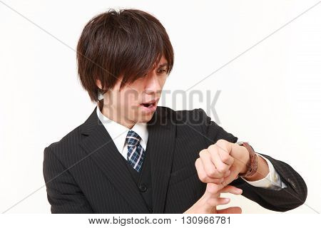 portrait of worried businessman looking at the wach on white background