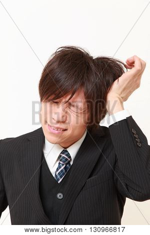 young Japanese businessman suffers from headache on white background