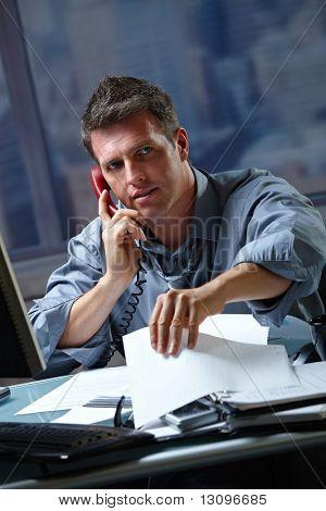Mid Kaufmann spricht über Festnetz Telefon Überstunden im Büro, die Papiere zu überprüfen.