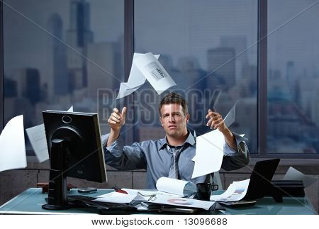 Exhausted businessman throwing documents into air sitting at office desk in overtime.