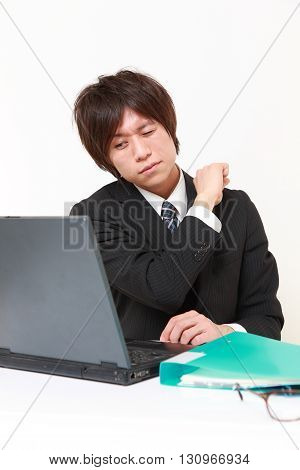 portrait of young Japanese businessman suffers from neck ache on white background