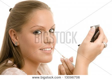 Beautiful young woman applying makeup, putting on lip liner, holding mirror. Isolated on white background.