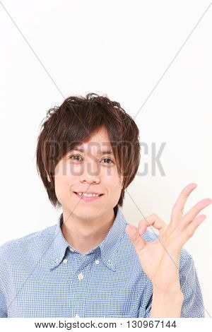 portrait of young Japanese man showing perfect sign on white background