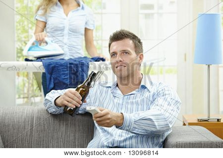 Man sitting at couch watching TV, woman ironing in the background. Selective focus on man.