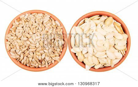 Two bowls of sunflower seeds and pumpkin isolated on white background. View from above.