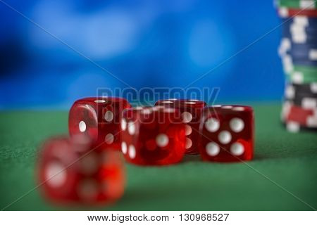 Red dice rotates on green felt, cards and casino chips